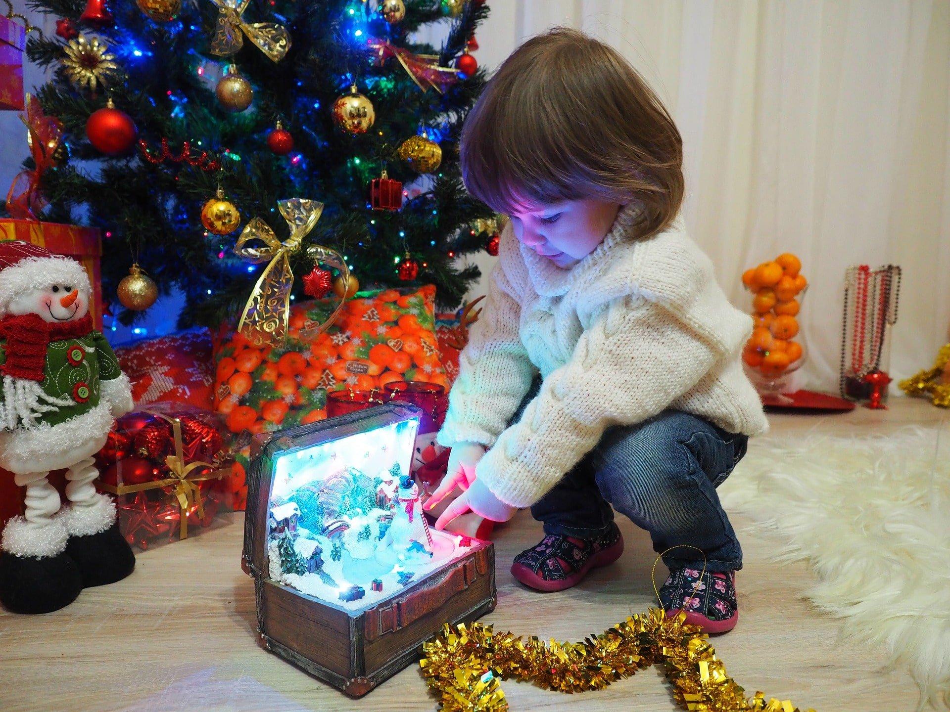 Niña jugando con un regalo.